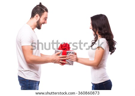 Valentine gift. Happy young couple with Valentine's Day present isolated on a white background. Happy man giving a gift to his girlfriend hand to hand. He look at present. Holiday