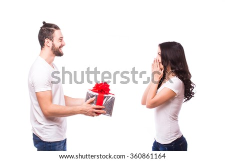 Valentine gift. Happy young couple with Valentine's Day present isolated on a white background. Happy man giving a gift to his girlfriend.She looks shocked surprised at him. Holiday - stock photo