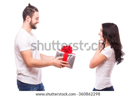 Valentine gift. Happy young couple with Valentine's Day present isolated on a white background. Happy man giving a gift to his girlfriend.  She looks happy at him. Holiday - stock photo