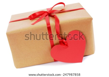 Valentine gift or package with red ribbon and heart shape gift tag isolated on a white background.  Space for copy. - stock photo