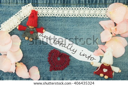 Valentine, greeting card with knitting couple in love, knitting red heart and soft pink rose petals. Lettering I am totally into you on the denim background. Handmade concept - stock photo