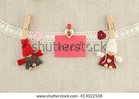 valentine, greeting card. Wooden pins, red and pink hearts, knitted loving couple man and woman, lettering I need you hanging on a clothesline. On the cloth background. - stock photo