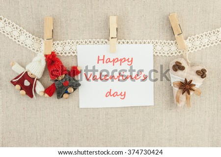 Valentine, greeting card. Wooden white heart, pins,  knitted loving couple man and woman, coffee brown textile heart,  lettering happy valentine's day hanging on a clothesline. On the cloth background - stock photo