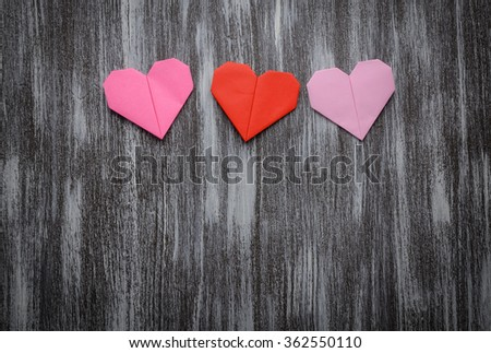 Valentine greeting paper folded origami love heart on wooden background - stock photo