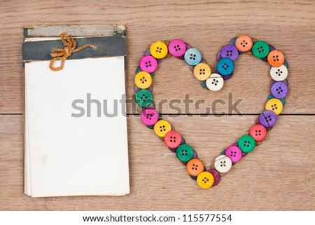 Valentine Heart and vintage notepad on wooden background - stock photo