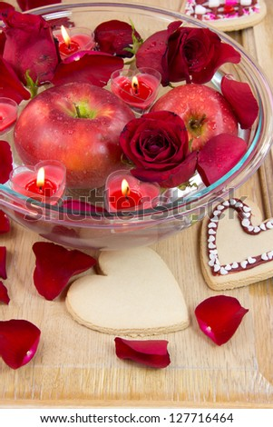 Valentine heart candles in bowl with rose petals and apple