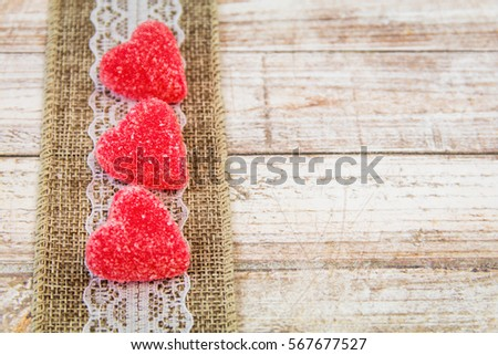 Valentine heart candy and burlap lace ribbon on wooden board with room for copy