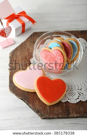 Valentine heart cookies in glass bowl with present box on wooden background