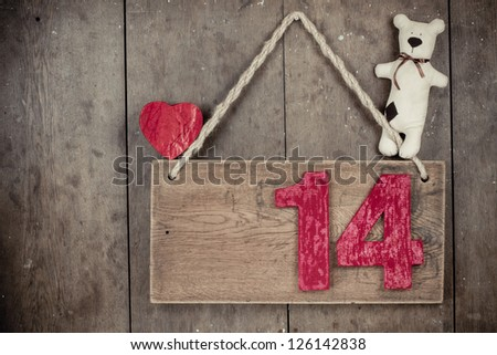Valentine heart, handmade teddy bear,  fourteen on wooden signboard with rope hanging on planks background - stock photo