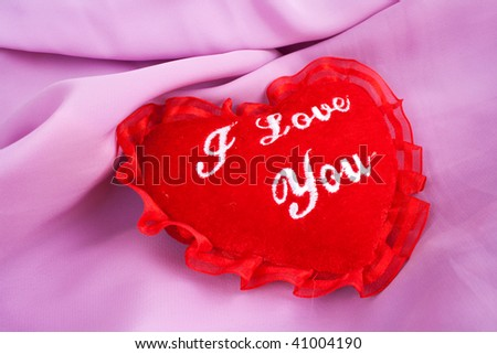 Valentine heart - soft pillow with I love you embroidering. Valentine's Day heart shaped pillow. Fluffy soft red heart over pink satin. - stock photo