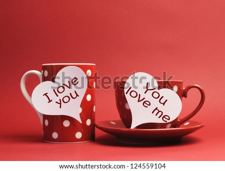 """Valentine """"I Love You"""" and """"You Love Me"""" messages written on heart tag signs on red polka dot mug, and cup and saucer against a red background. - stock photo"""