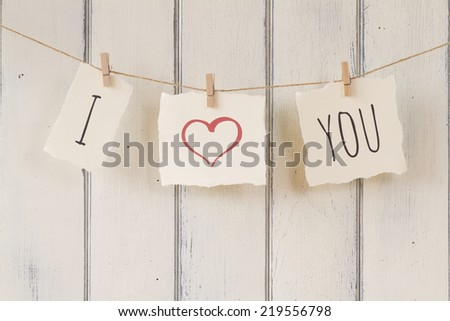 "Valentine. ""I love you"" hanging on a rope with clothespins. A white wooden wainscot as background. Vintage Style. - stock photo"
