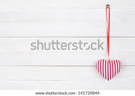 Valentine love heart hanging on vintage white wood background - stock photo
