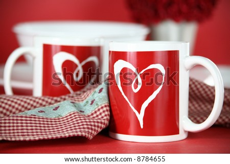 Valentine Morning: The table is set for a romantic breakfast for two. Two red and white heart mugs with dishware and roses in the background.