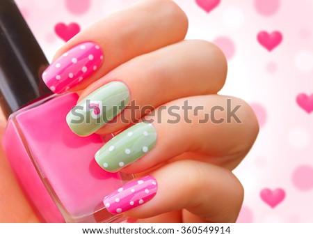 Valentine Nail art manicure. Valentine's Day Holiday style bright Manicure with painted hearts and polka dots. Bottle of Nail Polish. Beauty salon. Hand. Trendy Stylish Colorful Nails, Nailpolish - stock photo