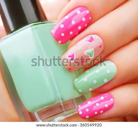 Valentine Nail art manicure. Valentines Day Holiday style bright Manicure with painted hearts and polka dots. Bottle of Nail Polish. Beauty salon. Hand. Trendy Stylish Colorful Nails, Nailpolish - stock photo