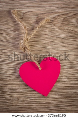 Valentine pink wooden heart with twine on wooden background, decoration for Valentines Day, symbol of love, copy space for text - stock photo