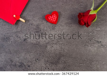 Valentine red heart, rose and love letter in red envelope on structure of concrete, decoration for Valentines Day, copy space for text - stock photo