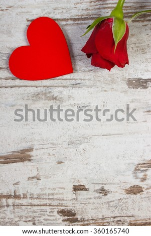 Valentine red wooden heart and rose on old wooden background, decoration for Valentines Day, copy space for text - stock photo