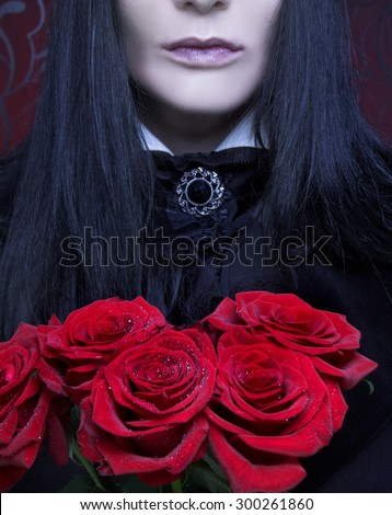 Valentine. Romantic portrait of young woman in gothic man image posing with red roses - stock photo