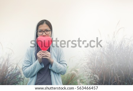 Valentine's concept. Asian woman holding red heart on flower grass field with fog background. Copy space. Vintage or retro color. Winter.