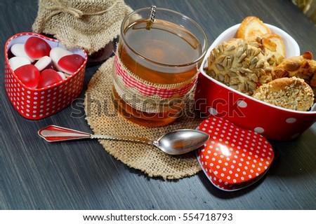 Valentine's concept. Heart shaped box, cookies with grains and candy in the shape of hearts and tea