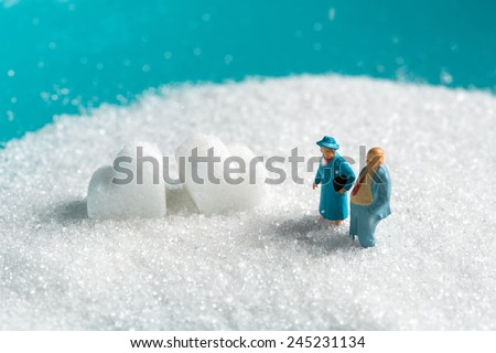 Valentine's Day,a miniature Senior couple walking on the snow in winter time with White Sugar in heart shape  - stock photo