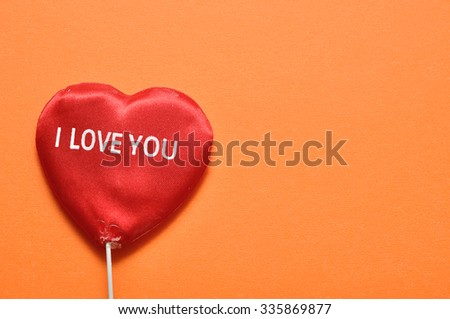 Valentine's Day. A red heart with I love you written on it isolated on an orange background