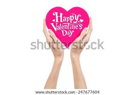 Valentine's Day and love theme: hand holds a greeting card in the form of a pink heart with the words Happy Valentine's day isolated on white background in studio - stock photo
