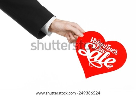 Valentine's Day and sale topic: Hand of a man in a black suit holding a card in the form of a red heart with the word Sale isolated on white background in studio. - stock photo