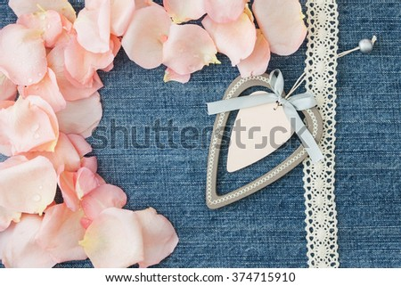 Valentine's day  background. Denim blue background with soft pink rose petals, white wooden heart. Valentine, greeting card, blank. Your text here - stock photo