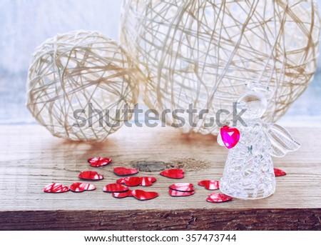 Valentine's day background with glass angel, wicker balls, confetti heart - stock photo