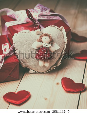 Valentine's day background with hearts and gifts on wooden table.
