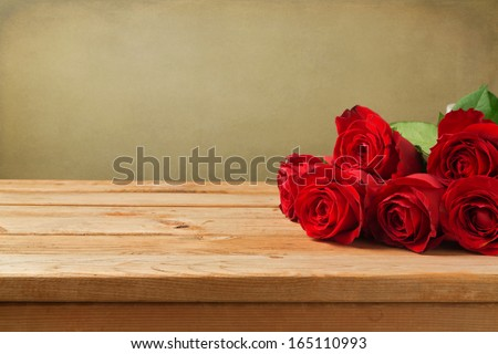 Valentine's day background with red roses on wooden table