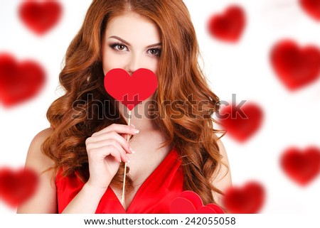 Valentine's Day. Beautiful redhair woman with hearts in her hands. Young woman with red hearts on white background. portrait of attractive smiling woman isolated on white studio shot with hearts - stock photo