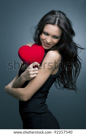 Valentine's Day. Beautiful smiling woman with a gift in the form of heart in his hands