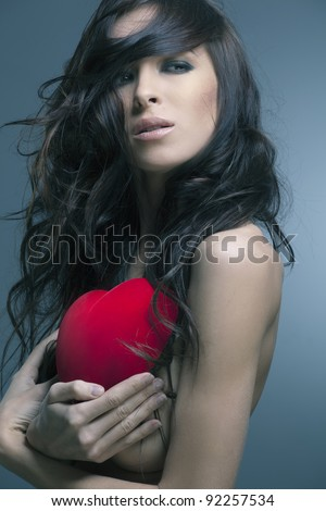 Valentine's Day. Beautiful woman with a gift in the form of heart in his hands - stock photo