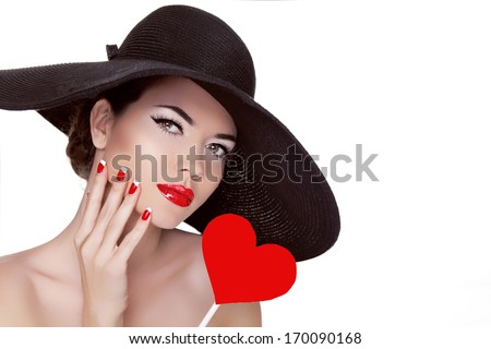 Valentine's Day. Beautiful woman with heart in her hand wearing in elegant hat. Makeup. Manicured nails. Beauty portrait of attractive girl. - stock photo