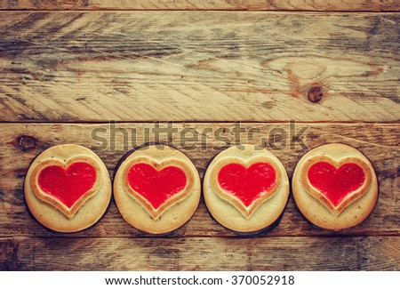 Valentine's Day border cookies with jam on wooden table - stock photo