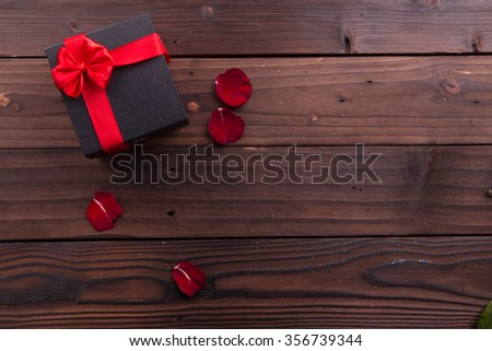 Valentine's Day: box gift with ribbons and red roses petals on rustic brown wooden background