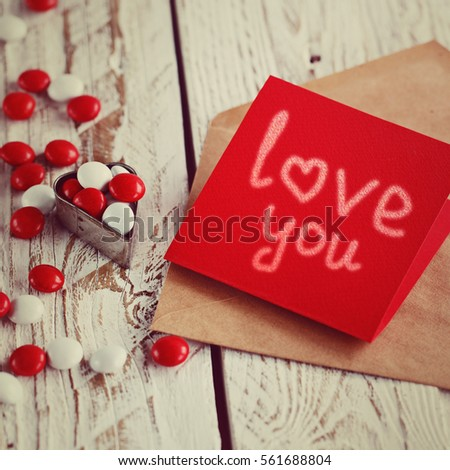 Valentine's day card with small hearts and red white candy on light wooden background. Toned image.