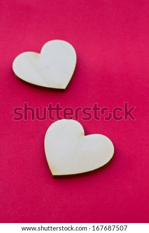 Valentine's day card with two wooden hearts on red surface