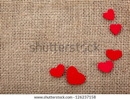 Valentine's day card with wooden red hearts symbol on fabric sack surface texture background - stock photo