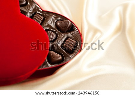 Valentine's Day chocolate gift set on smooth satin. Heart shaped velvet candy box with room for copy space.