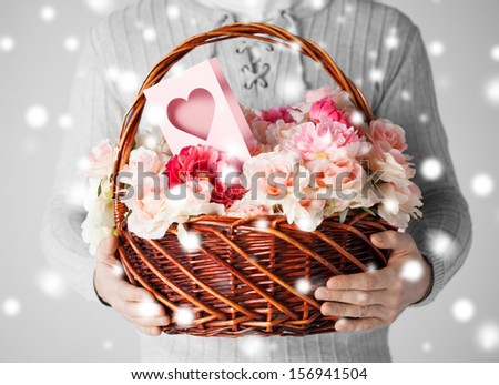 valentine's day, christmas, x-mas, winter, happiness concept - man holding basket full of flowers and postcard - stock photo