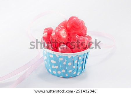 Valentine's Day Closeup of Candy, Foil wrapped chocolate hearts, Ribbon, Valentines hearts on a white background - stock photo