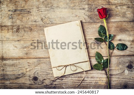 Valentine�´s day composition of a love journal and a red rose. Studio shot on a wooden floor background.