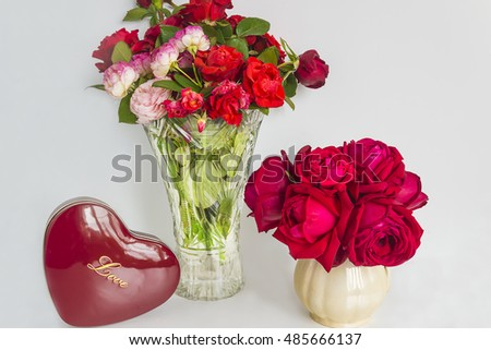 valentine's day composition/red gift box shaped heart and two bouquets of roses on a white background