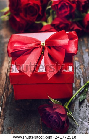 Valentine's day composition with hearts, gift, chocolate and flowers on wooden background