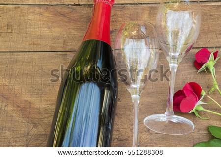 valentine's day concept/bottle of champagne, two empty glasses and red roses flowers on vintage wooden background